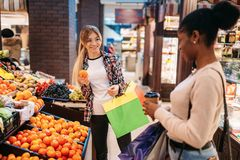 Black and white women buying fruits after shopping royalty free stock photography