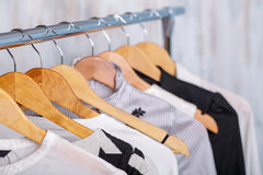 Black and white womens clothes on hangers on rack in fashion sto. Black and white womens clothes on wooden hangers on a rack in a fashion store. closet business stock image