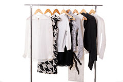 Black and white womens clothes on hangers on rack on white backg. Black and white womens clothes on wooden hangers on a rack on white background. closet business stock images