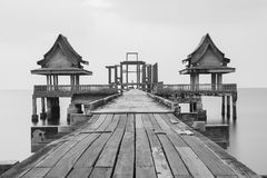 Black and white, wooden bridge leading to unfinished temple building Stock Image