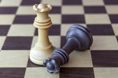 Black and white wooden kings on chessboard royalty free stock photo