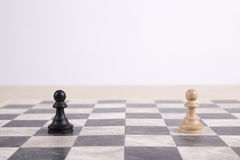 Black and white wooden pawns on chessboard Royalty Free Stock Photography