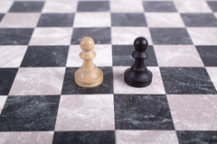 Black and white wooden pawns on chessboard Stock Images