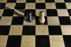 Challenge concept. Black and white wooden pawns on empty chess board Royalty Free Stock Image
