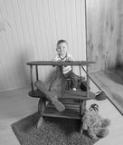 Black and white, on a wooden plane, playing a boy child Royalty Free Stock Photos