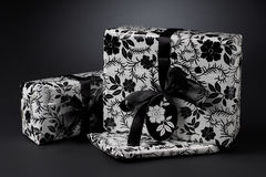 Black and white wrapped gifts. A black and white studio view of gift boxes wrapped in floral paper Royalty Free Stock Photo