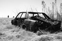 Black And White Wrecked Car. Wrecked car shot in black and white next to a road Stock Photography