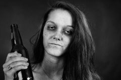 Black and white of young woman addict. Dramatic black and white portrait of a young woman addict with beer, junkie, alcohol or drug addiction Royalty Free Stock Photo