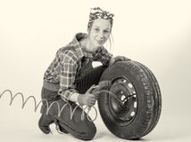 Black and white young woman inflates a car tire Royalty Free Stock Images