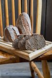 Black whole wheat sourdough bread. On a wooden chair royalty free stock photos