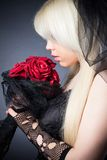 Black widow in grief  with flowers  with a veil Royalty Free Stock Photos