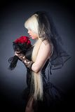 Black widow in grief  with flowers  with a veil. On a black background Stock Photos