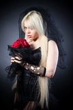 Black widow in grief with flowers with a veil. On a black background royalty free stock image