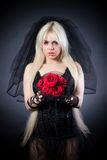 Black widow in grief with flowers with a veil. On a black background stock photo