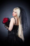 Black widow in grief  with flowers  with a veil Stock Photography