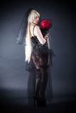 Black widow in grief with flowers with a veil. On a black background royalty free stock images