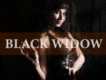 Black widow written on virtual screen. hand of young woman melancholy and sad at the window in the rain. Stock Photos