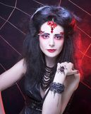 Black widow. Young woman in dark artistic image posing with spider Royalty Free Stock Photography