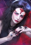 Black widow. Young woman in dark artistic image posing with spider Royalty Free Stock Image
