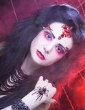 Black widow. Young woman in dark artistic image posing with spider Stock Photography