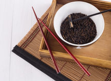 Black wild rice in a ceramic bowl with chopsticks on an oriental bamboo background. Organic healthy black wild rice in a white ceramic bowl with chopsticks with royalty free stock images