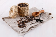 Black wild rice in a straw basket on a white wooden background. Organic healthy black wild rice in a straw basket with linen napkin and wooden scoop on a white royalty free stock image
