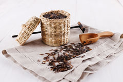 Black wild rice in a straw basket on wooden background. Organic healthy black wild rice in a straw basket with linen napkin and wooden scoop on a white wooden royalty free stock photography