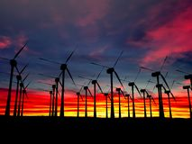Black Wind Turbines Field on a sunset background Royalty Free Stock Images