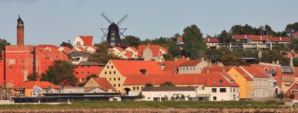 Black windmill and houses in Ebeltoft, Denmark. Old factory and beautiful black windmill in Ebelstoft, Djursland. Town at the east coast of Denmark Royalty Free Stock Photo