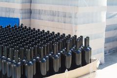 Free Black Wine Bottles On Pallets In Outside Storage Area Royalty Free Stock Images - 156509139