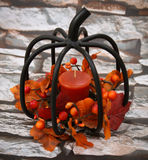 Black Wire Shaped Pumpkin Candle holder. With orange autumn leaves and berries Stock Photos