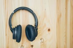 Black wireless headphones hang on a wooden wall. royalty free stock photography