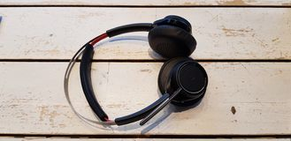 Black wireless headphones lay on white wooden table stock photography