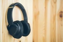 Black wireless large headphones hang on the nail on a natural wooden wall. Music and technology stock images