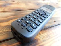 Black wireless phone. From an angle of a black wireless telephone view on a dark wooden base stock image