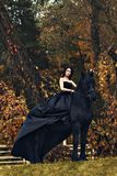 Black witch queen horseback on a black horse in a gloomy grim dark forest as in a horror scary fairy tale. A Black witch queen horseback on a black horse in a royalty free stock image