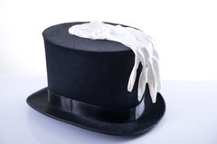 Black wizard top hat with white glove. Studio shot on white background with reflection Royalty Free Stock Images