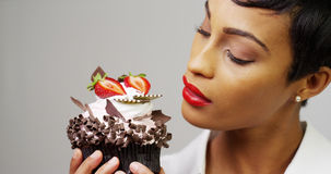 Black woman admiring a fancy dessert cupcake Royalty Free Stock Images