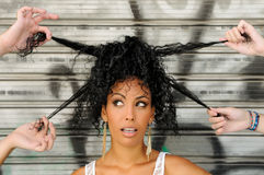 Black woman, afro hairstyle, in the city. Portrait of a young black woman, afro hairstyle, in urban background with four hands playing with her hair Stock Photos