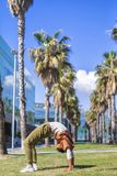 Black woman, afro hairstyle, doing yoga asana under the palms in a promenade stock photography