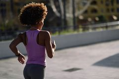 Black woman, afro hairstyle, running outdoors at Sunset. Rear view og black woman, afro hairstyle, running outdoors in urban road. Young female exercising in Royalty Free Stock Photo