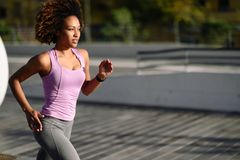 Black woman, afro hairstyle, running outdoors in urban road. Young female exercising in sport clothes Royalty Free Stock Photo