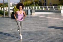 Black woman, afro hairstyle, running outdoors in urban road. Young female exercising in sport clothes Royalty Free Stock Images
