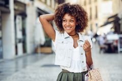 Black woman, afro hairstyle, with shopping bags in the street. Young black woman, afro hairstyle, with shopping bags in the street. Girl wearing casual clothes stock photos