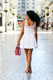 Black woman, afro hairstyle, walking barefoot. Portrait of a young black woman, afro hairstyle, walking barefoot on a commercial street Royalty Free Stock Photography