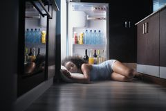 Black Woman Awake For Heat Wave Sleeping in Fridge. Young hispanic woman suffering for summer heat and lack of air conditioning at home. Black girl covered with stock photo