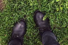 Black woman boots on green grass stock photo