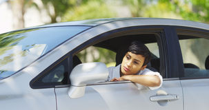 Black woman in car looking around and checking hair in mirror Royalty Free Stock Images
