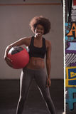 Black woman carrying crossfit ball Stock Photo