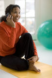 Black woman on cell phone. Smiling beautiful African American woman sitting on yoga mat talking on cell phone Stock Images